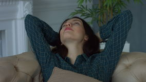 Cute woman relaxing on sofa with hands behind head stock footage
