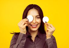 Cute woman removing applied makeup with a cotton sponge pad. Isolated on yellow background royalty free stock photography