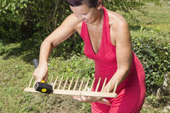 Cute woman repairing wooden rake Royalty Free Stock Photo