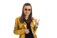 Cute woman in round sunglasses and golden jacket showing peace gesture. Isolated on white background royalty free stock images