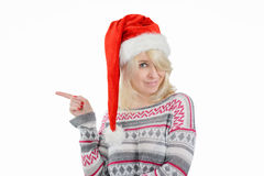 A cute woman in Santa's hat pointing right with finger. A young cute woman wearing Santa's hat pointing right with finger Stock Images