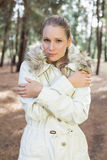 Cute woman shivering while having a walk in a forest Stock Image