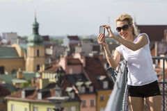 Cute woman shoots on a smartphone Warsaw's old town. Royalty Free Stock Image