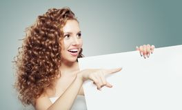 Cute woman showing white empty paper board background with copy space for advertising marketing or product placement and pointing.  royalty free stock photography