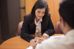 Cute woman signing a document Royalty Free Stock Photography