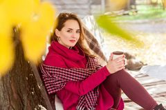 Cute woman sit on bench in autumn park, holding cup Stock Photos