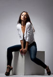 Cute woman sit in jeans and white jacket Stock Photography