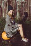 Cute woman sitting on autumn pumpkin Stock Images