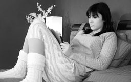 Cute woman sitting in bed relaxing looking social network on tablet black and white royalty free stock photo