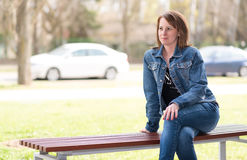 Cute woman sitting on the bench Stock Images