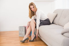 Cute woman sitting on couch taking off her shoes Royalty Free Stock Photo