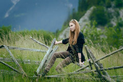 Cute woman sitting on fence Stock Photos