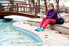 Cute Woman sitting in Park reading tablet device Stock Image