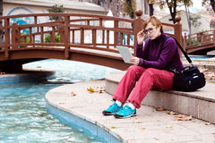 Cute Woman sitting in Park using tablet device Royalty Free Stock Photo