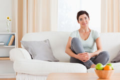 Cute woman sitting on a sofa Royalty Free Stock Photography