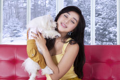 Cute woman sitting on sofa while holding dog Royalty Free Stock Photography