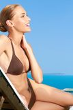 Cute woman sitting on sunbed and smiling. Cute young woman sitting on sunbed and smiling Royalty Free Stock Photo