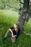 Cute woman sitting under tree Royalty Free Stock Photo
