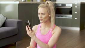 Cute woman sitting on yoga mat and browsing mobile phone for songs stock footage