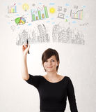 Cute woman sketching city and graph icons Stock Photos