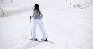 Cute woman on skis at bottom of hill Royalty Free Stock Image