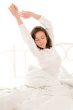 Cute woman stretching herself after sleep Stock Photo