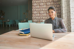 Cute woman successful freelancer using laptop computer while sitting in coffee shop. Young female student working on net-book with blank copy space screen for Royalty Free Stock Photos
