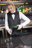 Cute woman in suit pouring champagne into flute Stock Photos