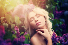 Cute Woman with Summer Light and Lilac Flowers Royalty Free Stock Photo