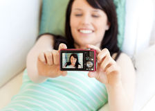 Cute woman taking picture of herself lying on bed Stock Image