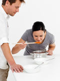 Cute woman tasting her soup with her husband Stock Image