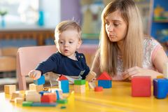 Cute woman teacher and child playing educational toys at kindergarten or nursery room royalty free stock photos