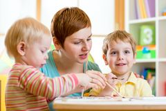 Cute woman teaching kids to paint Royalty Free Stock Images