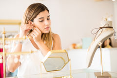 Cute woman trying on some earrings Stock Photos