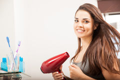 Cute woman using a blow dryer. Hispanic young woman drying her hair in front of a mirror in a bathroom and smiling royalty free stock photo