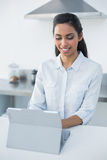 Cute woman using her tablet standing in bright kitchen Stock Photos
