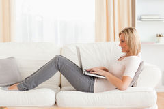 Cute woman using a laptop while lying on a sofa Stock Photos