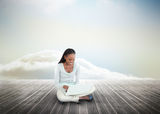 Cute woman using laptop over wooden boards leading out to the horizon Royalty Free Stock Image