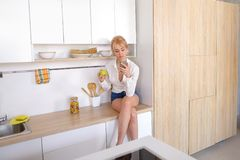Alluring female holding cell phone and eating apple, sitting on. Cute woman using modern device, mobile phone reads useful articles about nutrition or orders royalty free stock images