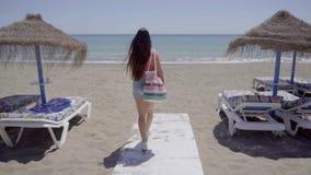 Cute woman walking on boardwalk to beach stock footage