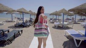 Cute woman walking on boardwalk to beach stock video footage