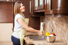 Cute woman washing vegetables Stock Photo