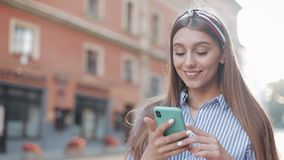 Cute woman wearing in blue and white striped dress using app on smartphone standing on the old city street. Beautiful. Girl having good news on smartphone stock video