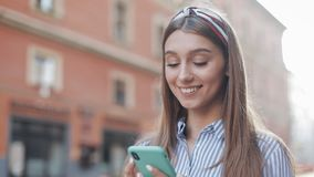 Cute woman wearing in blue and white striped dress using app on smartphone standing on the old city street. Beautiful. Girl having good news on smartphone stock footage