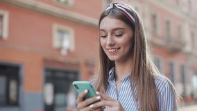 Cute woman wearing in blue and white striped dress using app on smartphone standing on the old city street. Beautiful. Girl having good news on smartphone stock video footage