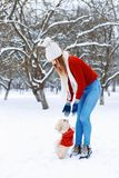 Cute woman in a white knitted sweater walking a Pekingese puppy. On a winter day on the background of the park Stock Images
