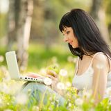 Cute woman with laptop in the park with dandelions Stock Photos