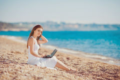 Cute woman with white laptop on the summer beach Stock Photography
