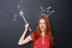 Cute woman winking with crown and magic wand over chalkboard Royalty Free Stock Photo