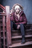 Cute woman in winter coat on staircase Stock Photos